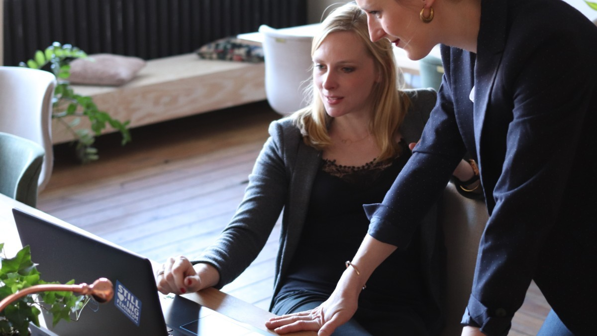 Two women on a computer deciding reading about MySQL vs MS SQL Server – Which Database Reigns Supreme?
