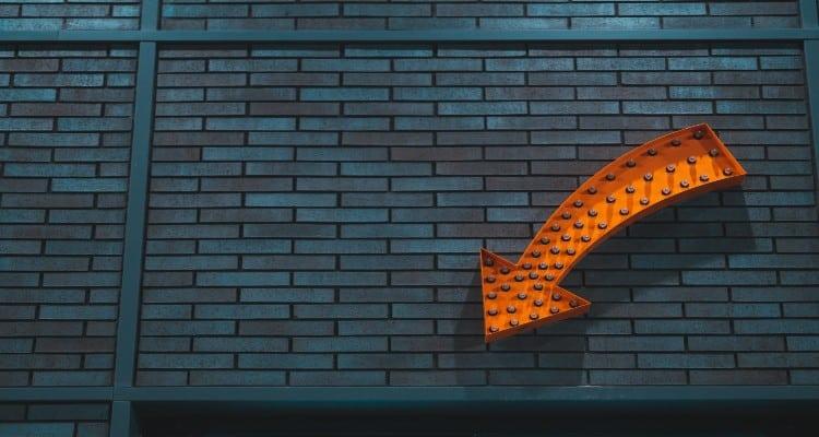 Brick wall with orange arrow